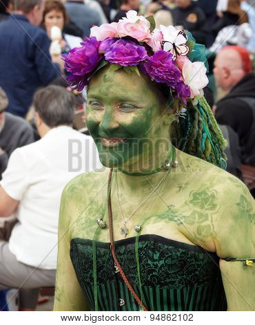 Woman in painted green with garlands hat