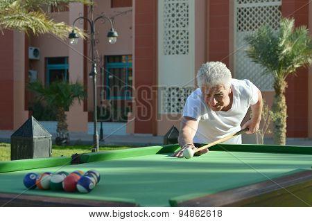 Amusing old man  playing billiards