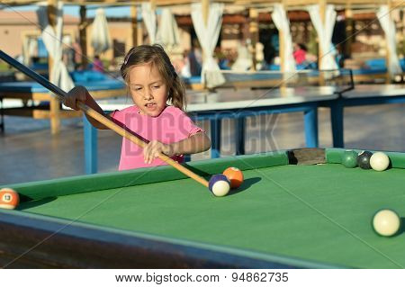 Amusing yong girl playing billiards