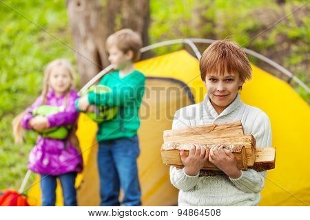 Boy holds the wood for camping bonfire in forest