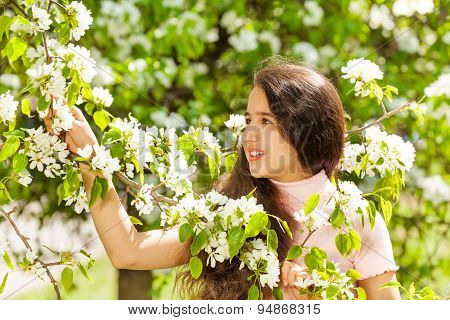 Teenager girl holding white flowers on pear tree