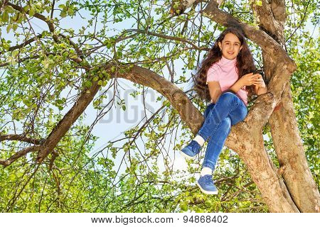 Girl sitting on the bench of tree in forest alone