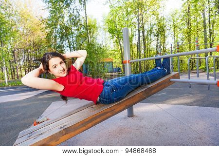 Girl is doing crunches on the wooden board alone