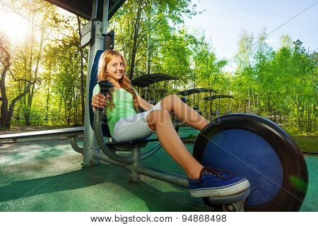 Cute teenage girl cycling on exercise equipment