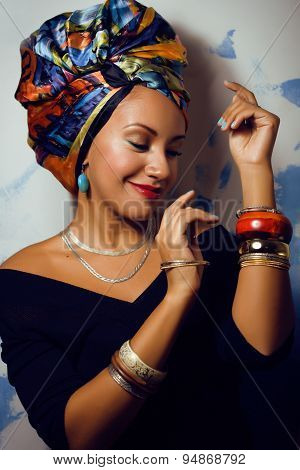 beauty bright african woman with creative make up, shawl on head like cubian closeup