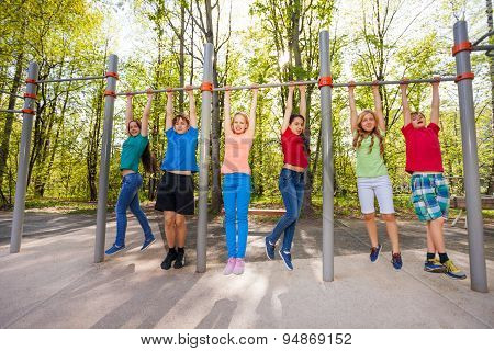 Happy teens chinning up on the playground