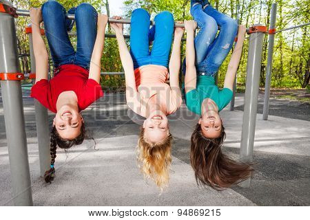 Three girls hanging upside-down on brachiating bar