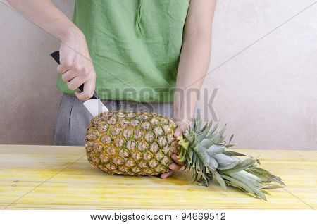 Woman Cutting A Pineapple Over Wood.