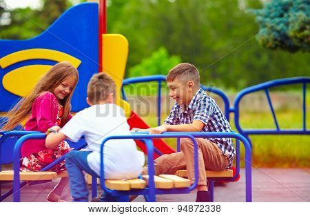 Happy Friends, Kids Having Fun On Roundabout At Playground