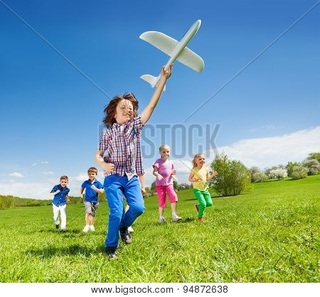 Positive running kids and boy holding airplane toy