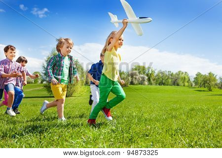 Running kids and girl holding white airplane toy