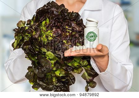 Young Doctor Holding Lettuce And Bottle Of Pills With Vitamins A