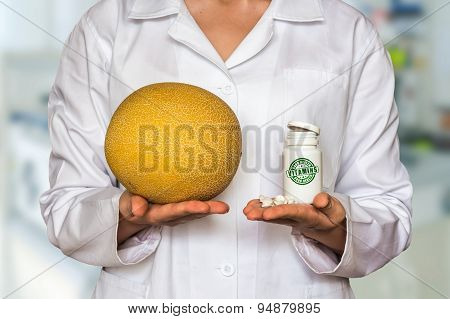 Young Doctor Holding Yellow Melon And Bottle Of Pills With Vitam