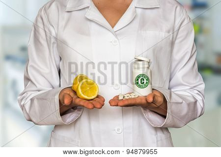 Young Doctor Holding Two Halves Of Lemon And Bottle Of Pills Wit