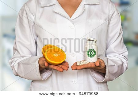Young Doctor Holding Two Halves Of Orange And Bottle Of Pills Wi
