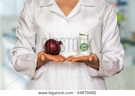 Young Doctor Holding Onion And Bottle Of Pills With Vitamins And
