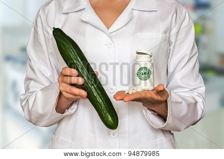 Young Doctor Holding Fresh Cucumber And Bottle Of Pills With Vit