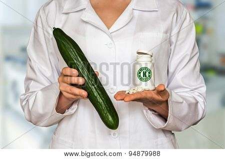 Young Doctor Holding Cucumber And Bottle Of Pills With Vitamin K