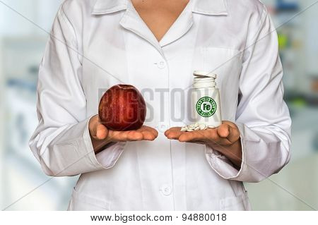 Young Doctor Holding Apple And Bottle Of Pills With Iron Fe, Com