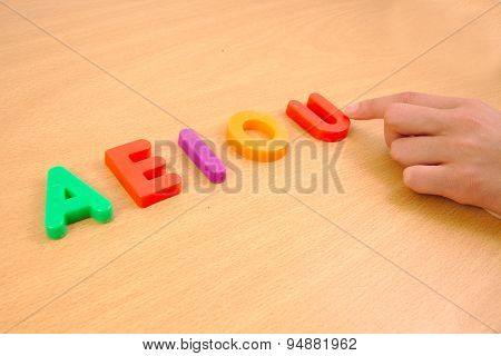 Letters a e i o and u with child hand, school concept