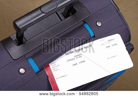 airline baggage receipt and suitcase