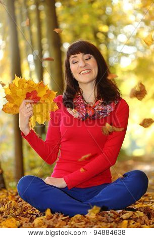 Smiling Woman In Autumn Park With Leaves In Hands