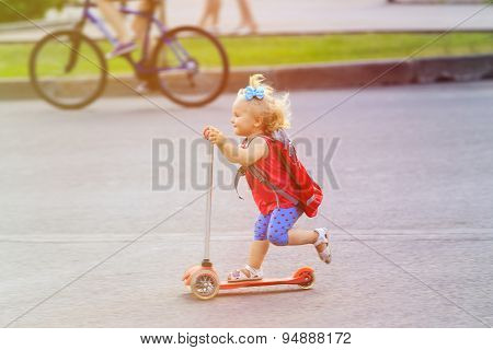 cute little toddler girl riding scooter in the city