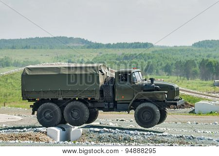 Army truck URAL-4320 jumps through obstacle