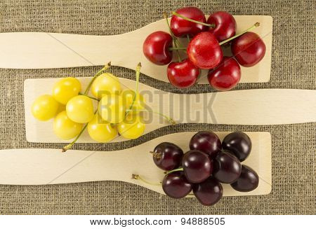 Colorful Cherries In A Wooden Spatula On A Natural Fabric