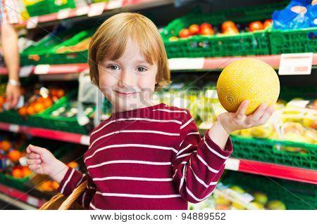 Little boy choosing fruits in a food store