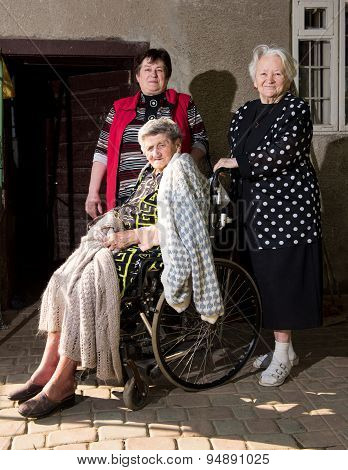 Old Woman In Wheel Chair With Family
