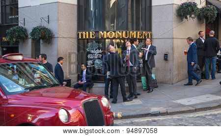 LONDON, UK - APRIL15, 2015: Exterior of pub in the City of London with lots of people drinking and s