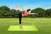 pic of yoga mat  - Young woman doing yoga exercise with yoga mat on green grass and blue sky - JPG