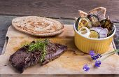 stock photo of cheval  - Provencal style horse meat entrecote steak with ratatouille and flat bread served on a wooden board decorated with lavender and fresh thyme - JPG