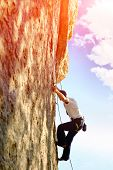 stock photo of climbing wall  - Young man climbs on a rocky wall - JPG