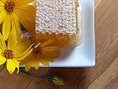 stock photo of jerusalem artichokes  - honeycombs and flowers of Jerusalem artichoke on a wooden table - JPG