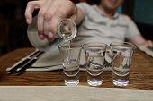 image of vodka  - Man pouring vodka into glasses in the pub - JPG