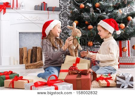 Cute happy excited children, boy and girl in santa hats unwrap rabbit christmas present on holiday morning in beautiful room. Sister and brother open Xmas gifts near decorated tree and fireplace.