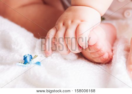 Baby is sitting on the textile. Hands and feet close up