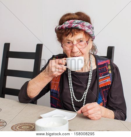Old grandmother drinking tea. Granny woman at home. Mature female