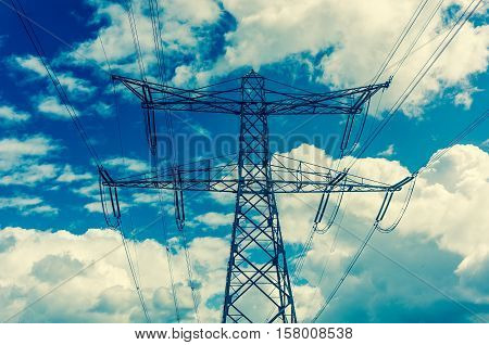Electric pylons on the blue sky background - retro style