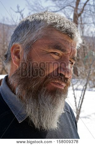 A portrait close-up of the old men with grey beard. Small indigenous peope of Russian Far East.