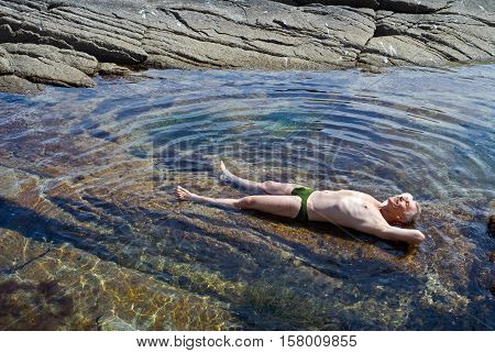 A man sunbathes in water among reefs. Summer sunny day.