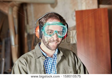 Carpenter with protective googles and ear protection