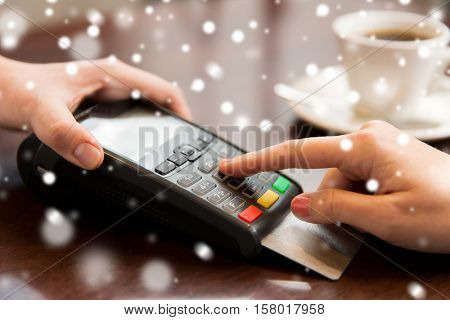 people, finance, payment, technology and consumerism concept - close up of waitress holding credit card reader and customer hand entering pin code at cafe over snow