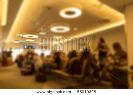 Defocused view of airline passengers waiting in terminal waiting for the delayed flight