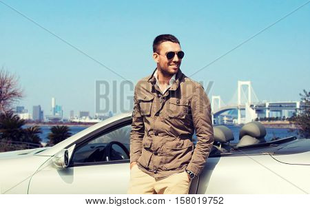 travel, tourism, transport, leisure and people concept - happy man near cabriolet car outdoors