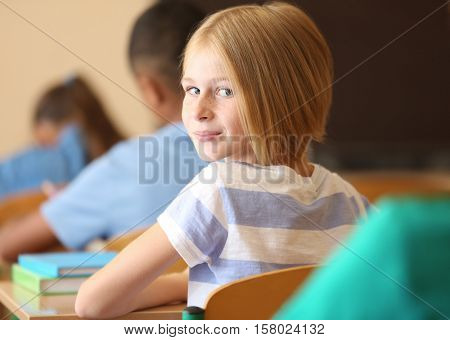 Cute schoolgirl on lesson in classroom