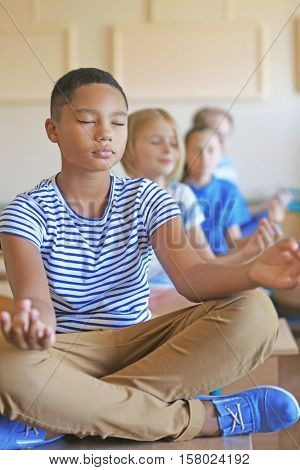 Schoolchildren in lotus position relaxing on lesson