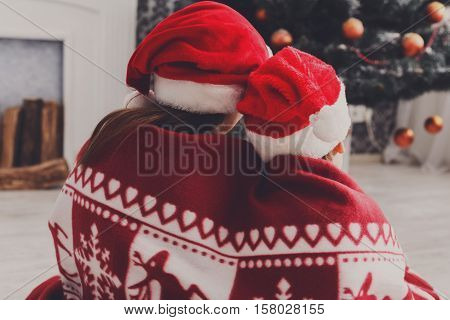 Adorable children in santa hats near christmas tree, wait for holiday gifts. Magic christmas atmosphere at cosy home. Boy and girl, brother and sister sit near fireplace wrapped up in blanket